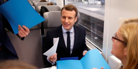 Emmanuel Macron, head of the political movement En Marche !, or Onwards !, and candidate for the 2017 presidential election, talks with staff members as he sits in a train en route to deliver a speech in Lille